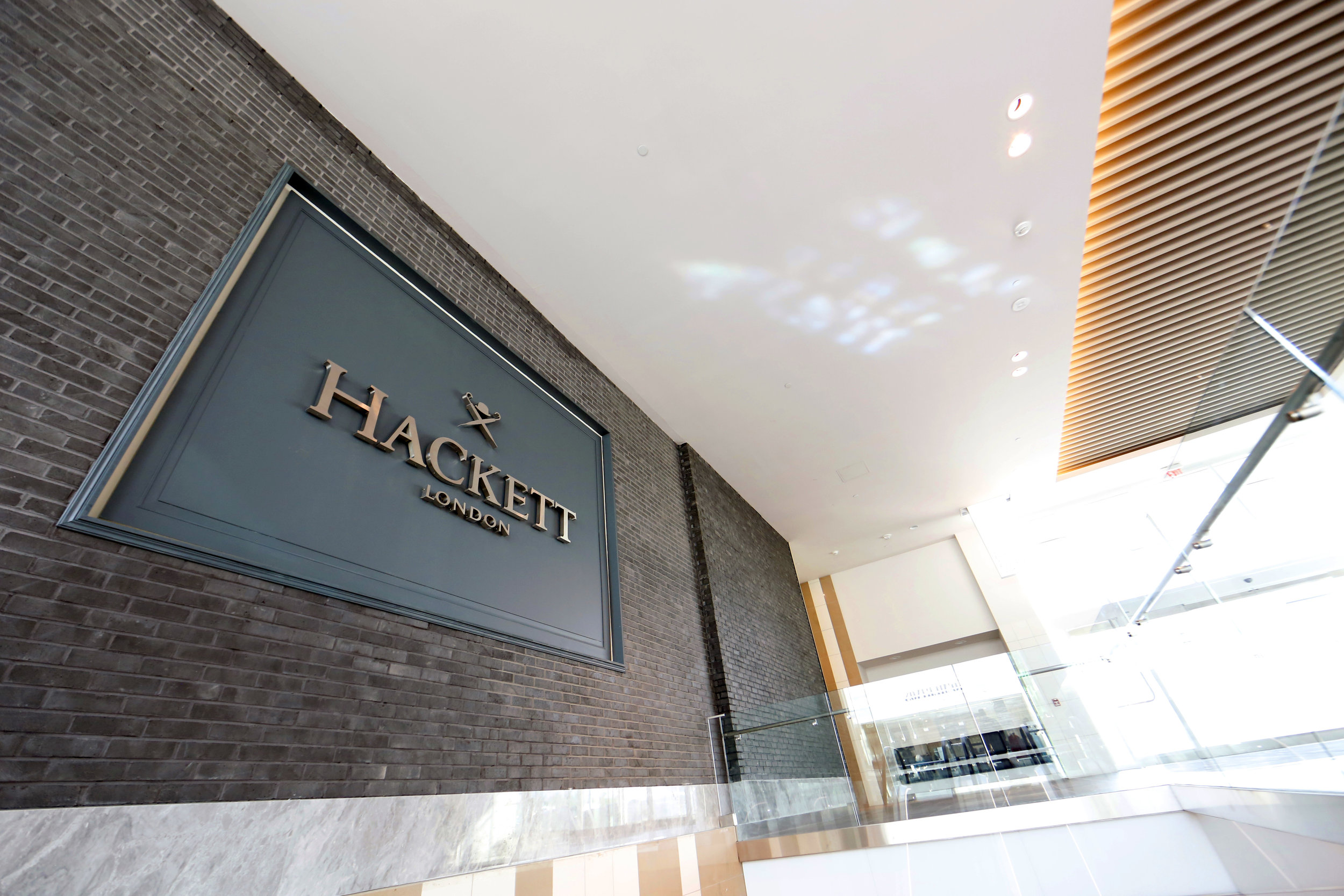 Dark grayish blue exterior signage of Hackett London in Woodbury Common Premium outlet. MEP designed by New York firm, 2L Engineering.