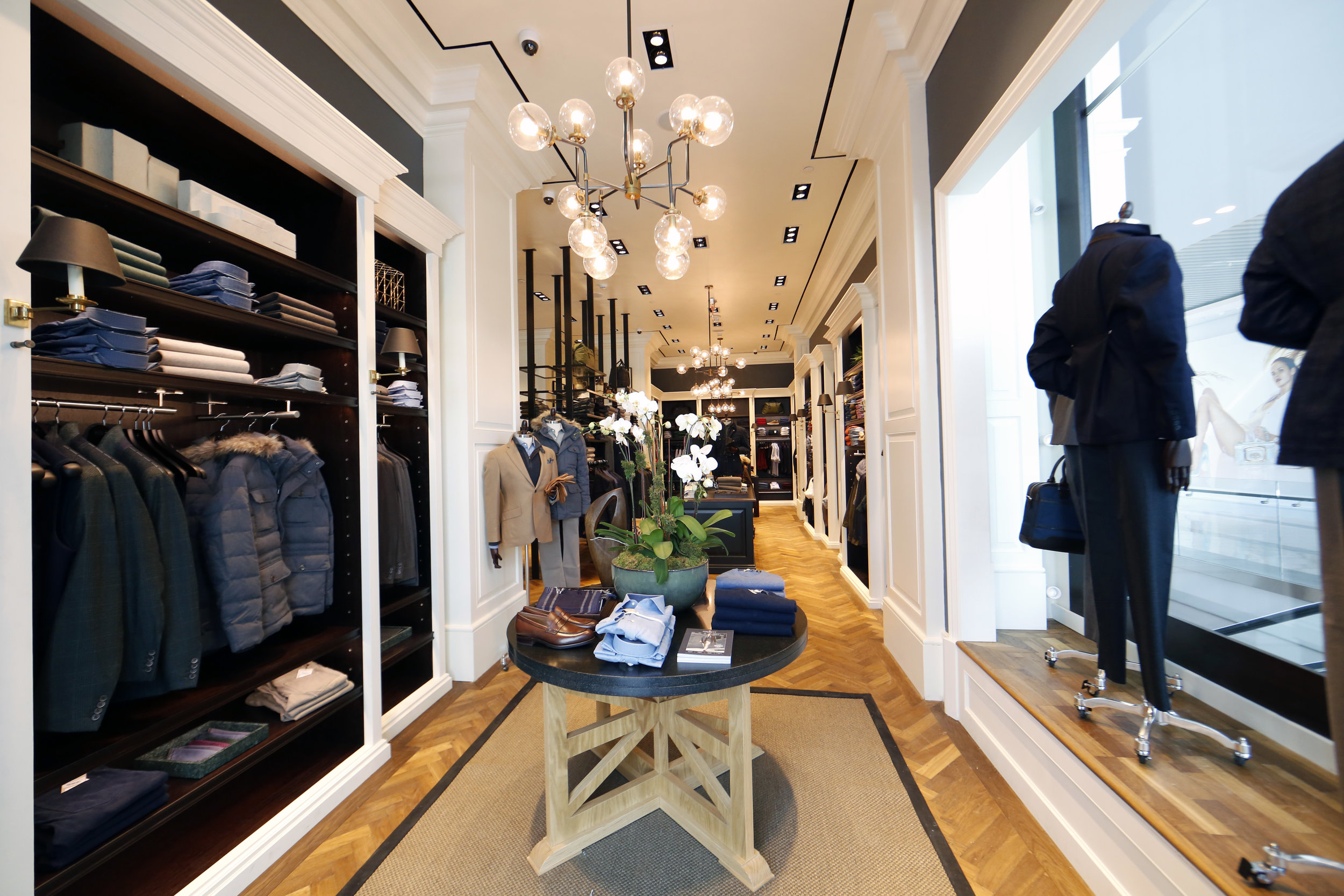 Orchids on a display table with collared shirts, a book, and brown leather loafers in Hackett London's Woodbury Common Premium outlet location. MEP by New York firm, 2L Engineering