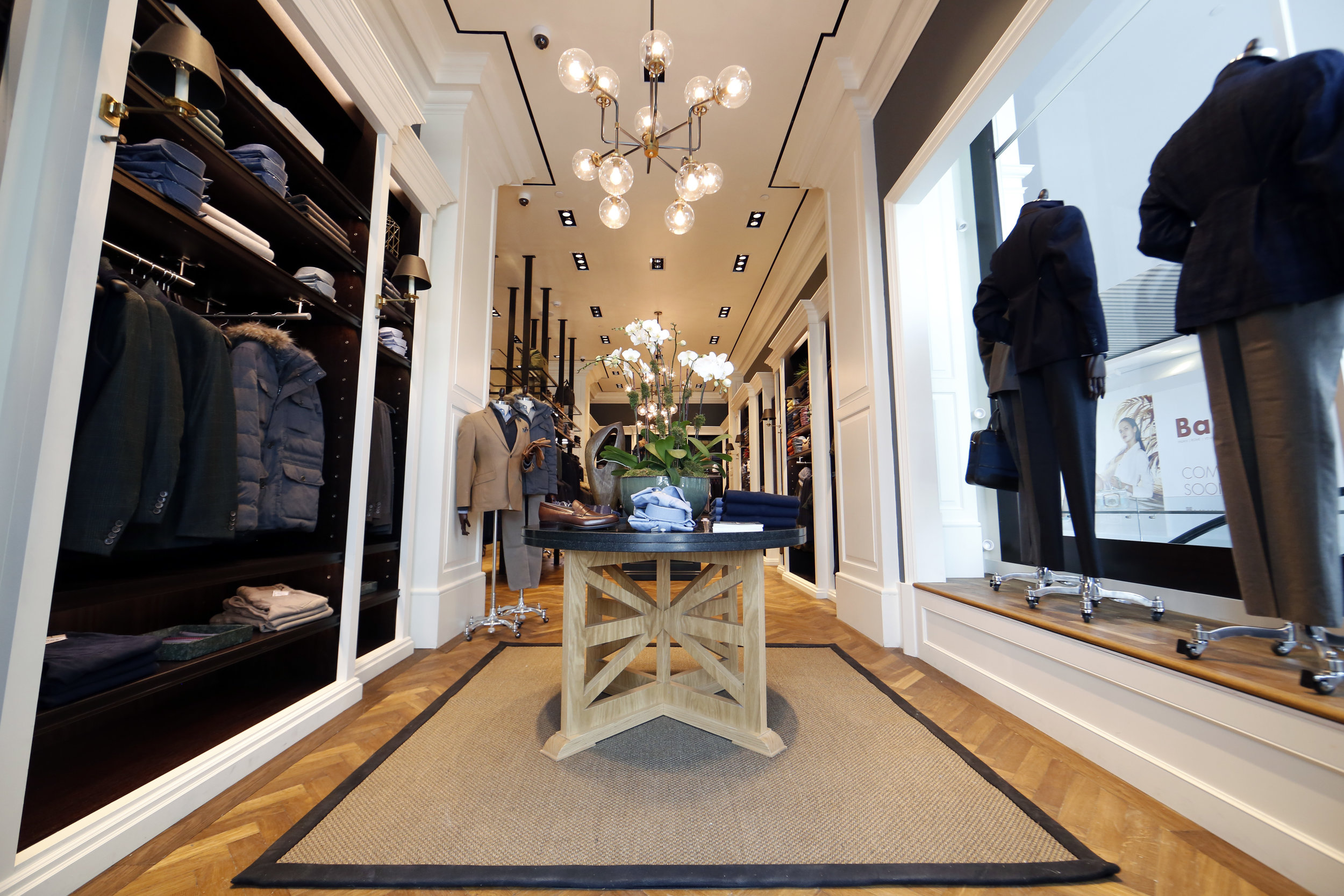 Brightly lit display table featuring winter fashion by Hackett London in Woodbury Common Premium outlet, New York. MEP designed by 2L Engineering.