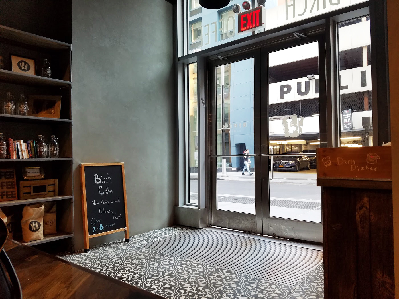Entrance for Birch Coffee, with a shelf to the side holding brand products. MEP provided by 2L Engineering.