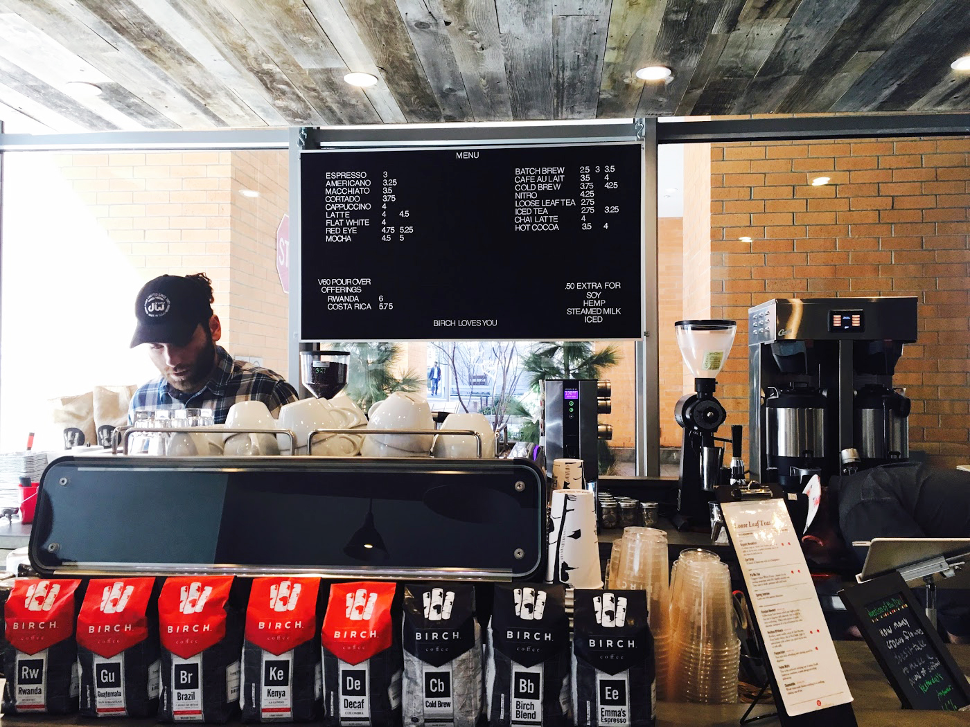 Barista brewing coffee in front of the Birch Coffee menu with Birch Coffee ground coffee on the counter. MEP provided by 2L Engineering.