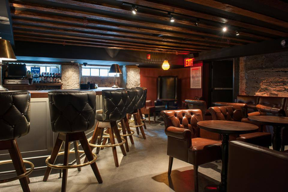 Leather seating throughout a room and by a bar in the basement of the Trading Post, a bar and restaurant in New York's Financial District. MEP provided by 2L Engineering.