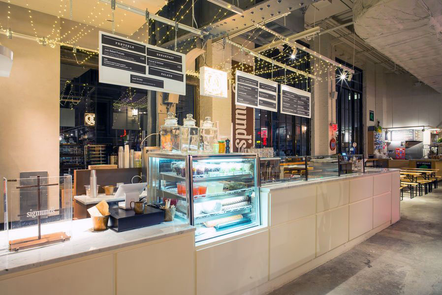 Sigmund's featuring drinks and food in a brightly lit display case located in Urbanspace Vanderbilt in Midtown Manhattan. MEP designed by 2L  Engineering.