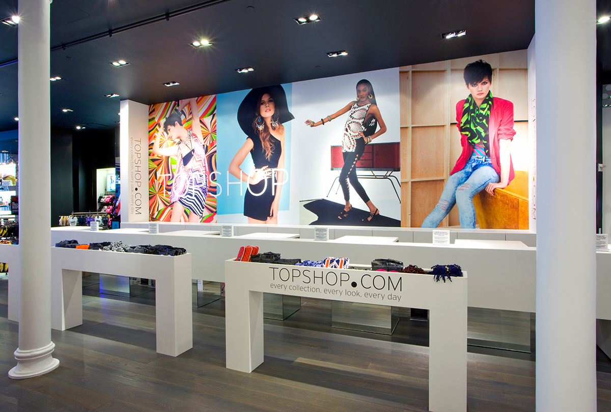 Cash registers and small display racks with large pictures of female models wearing Topshop clothing. MEP provided by 2L Engineering.
