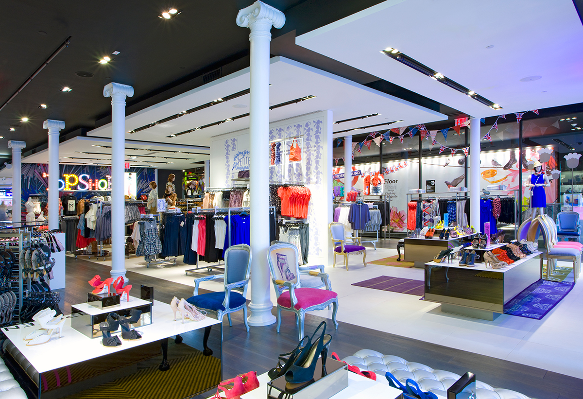Womens shoes on display shelves with a seating area in Topshop / Topman New York. MEP designed by 2L Engineering.