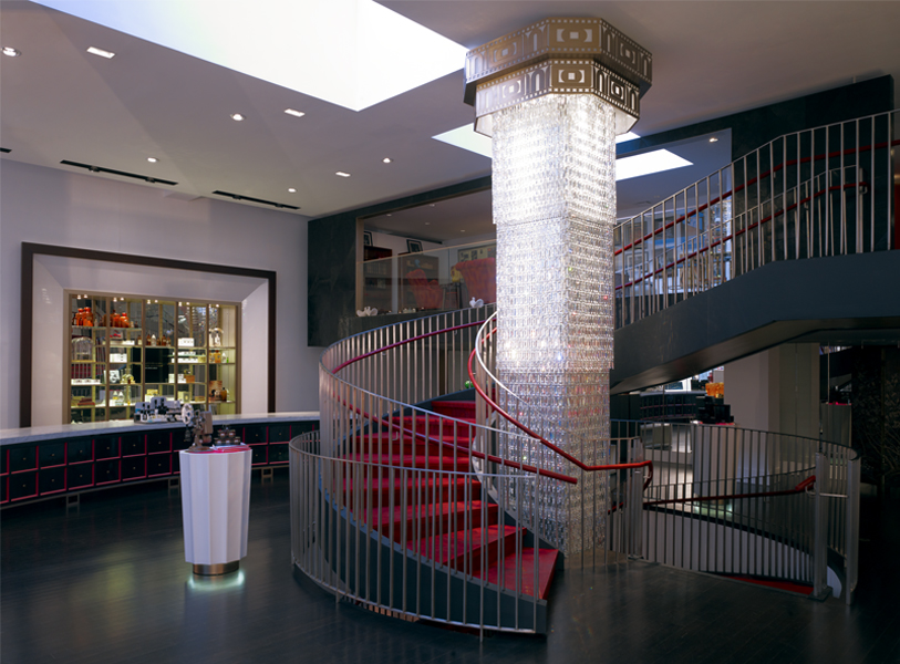 Wide shot of the spiral staircase from the ground floor featuring a decorated column and a small table to the side with skincare products. MEP by 2L Engineering.