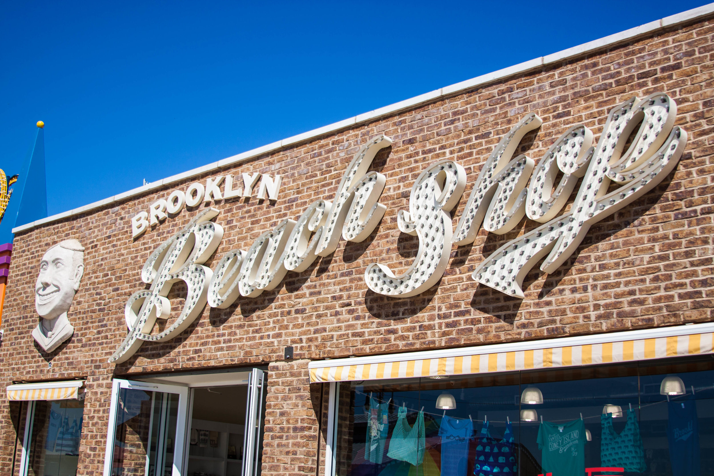 Vintage signage on the brick wall exterior of the Brooklyn Beach Shop, a retail space on the Coney Island Boardwalk with a new facade. MEP designed by 2L Engineering.