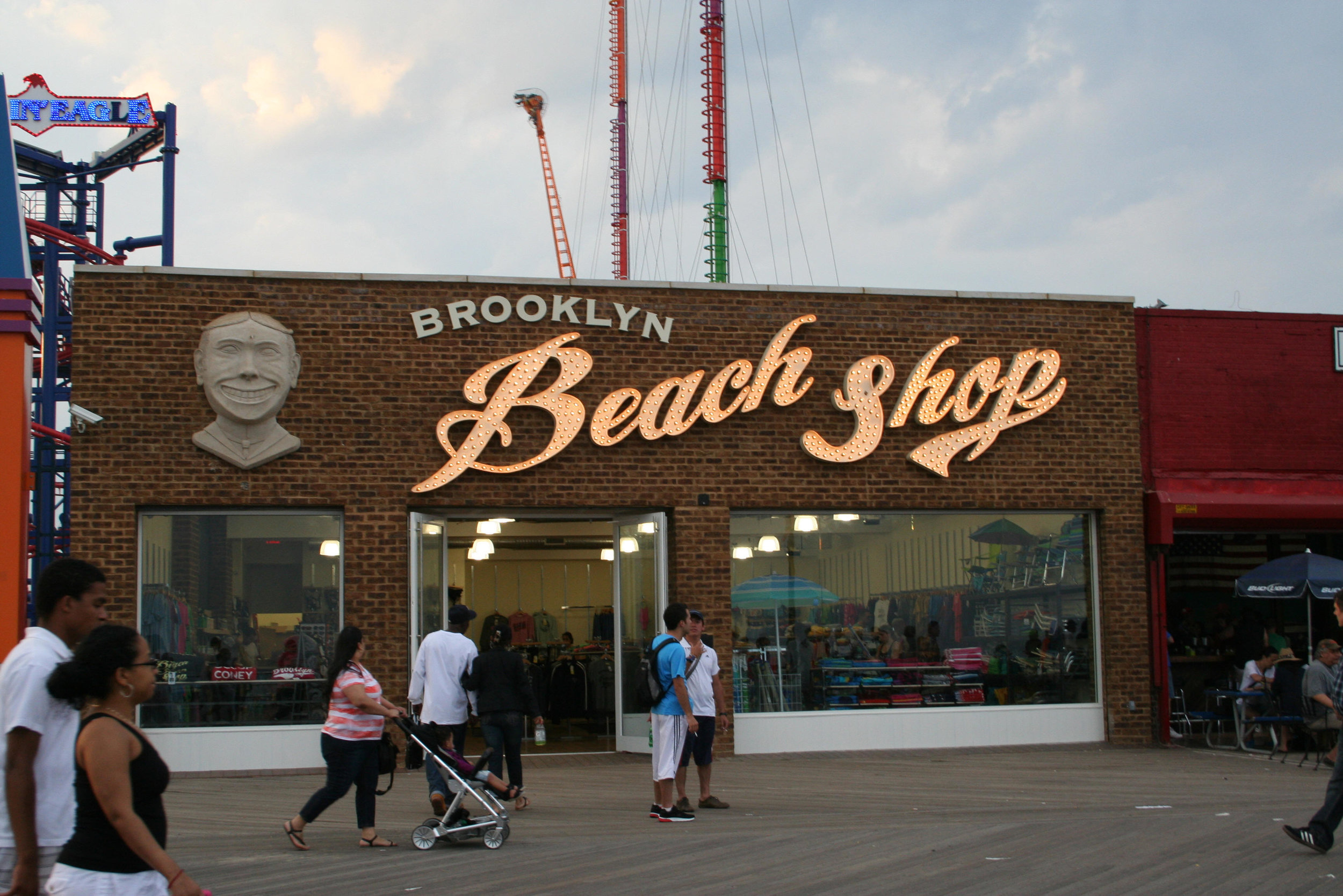 People walking by and a woman pushing a stroller by the Brooklyn Beach Shop on the Coney Island Boardwalk. MEP designed by 2L Engineering.