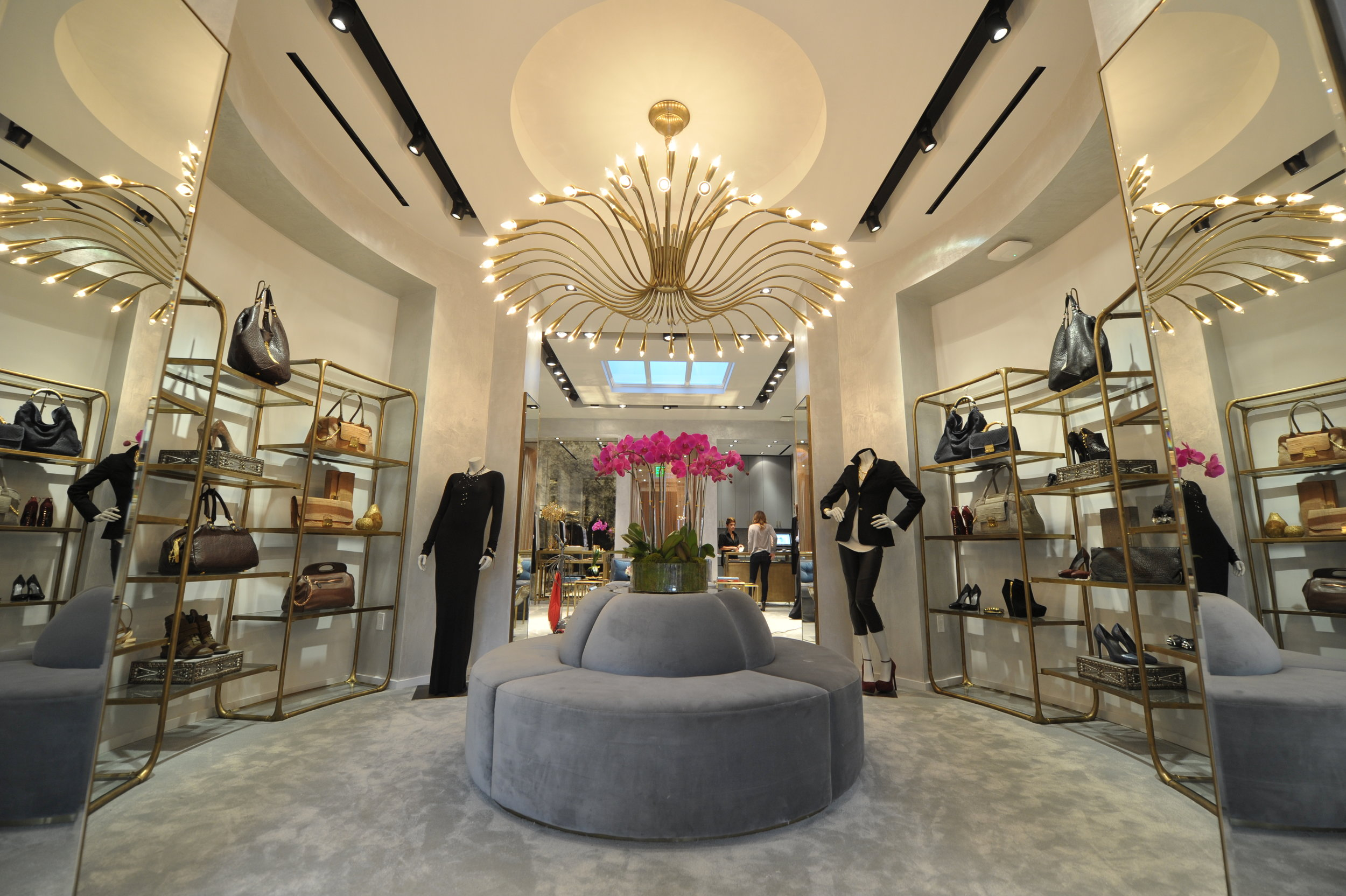 Large wiry chandelier over a grey circular couch and grey carpet surrounded by display shelves featuring handbags and shoes by Monika Chiang. MEP designed by 2L Engineering.