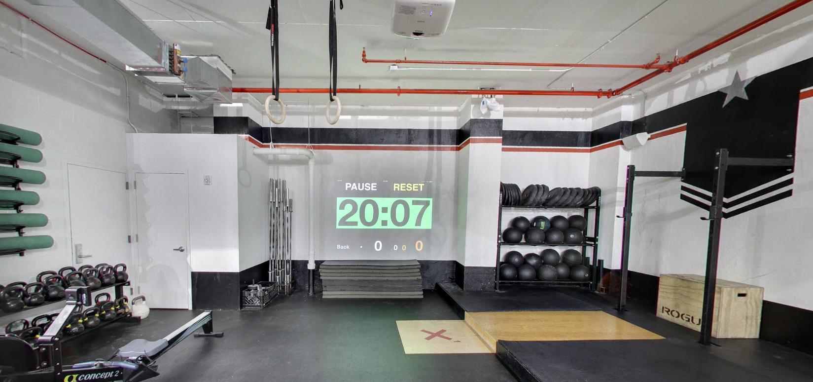 A timer projected on the wall beside mats, weights and other fitness equipment in Crossfit Tribeca with MEP designed by 2L Engineering.