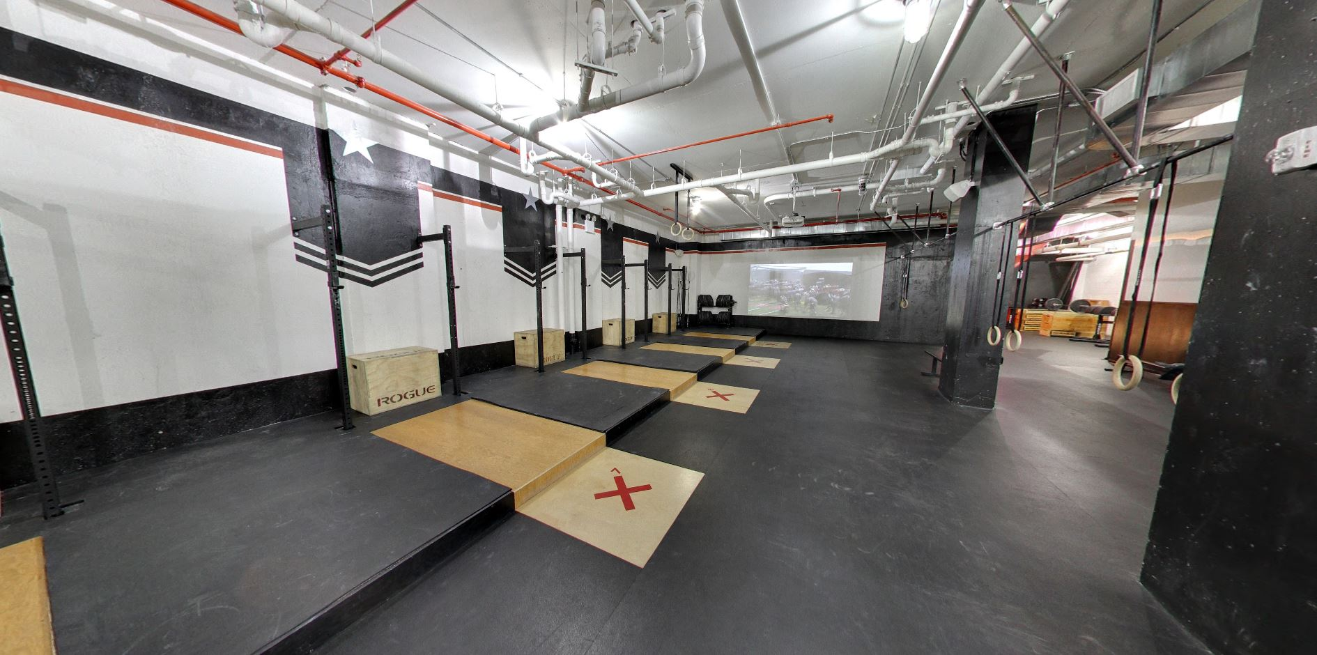 Different stations and an image projected on the wall in the fitness studio of the Crossfit Tribeca location in New York with MEP designed by 2L Engineering.
