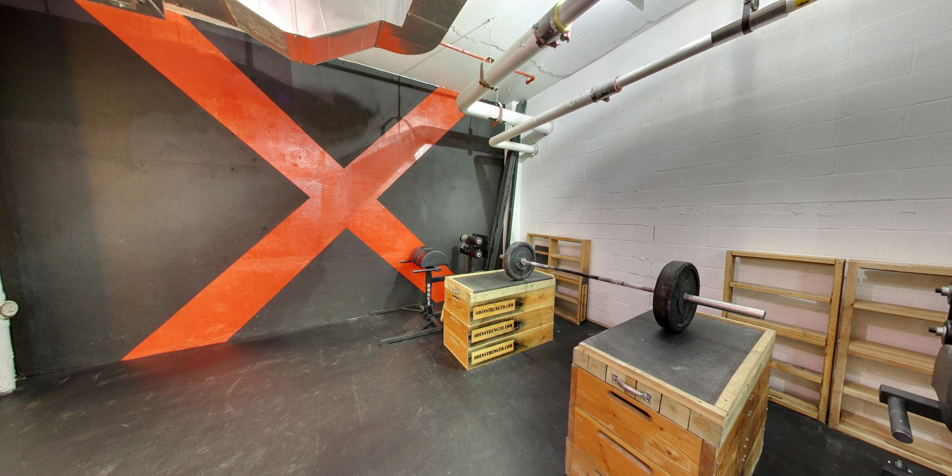 Weights resting over boxes with a giant orange red cross painted over a black wall as part of the Crossfit brand in it's Tribeca location. MEP designed by 2L Engineering.