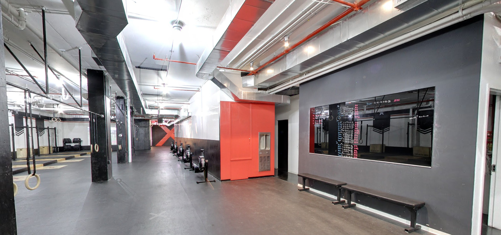 A bright red wall surrounded by fitness equipment and benches in the Tribeca location of Crossfit with MEP designed by 2L Engineering.