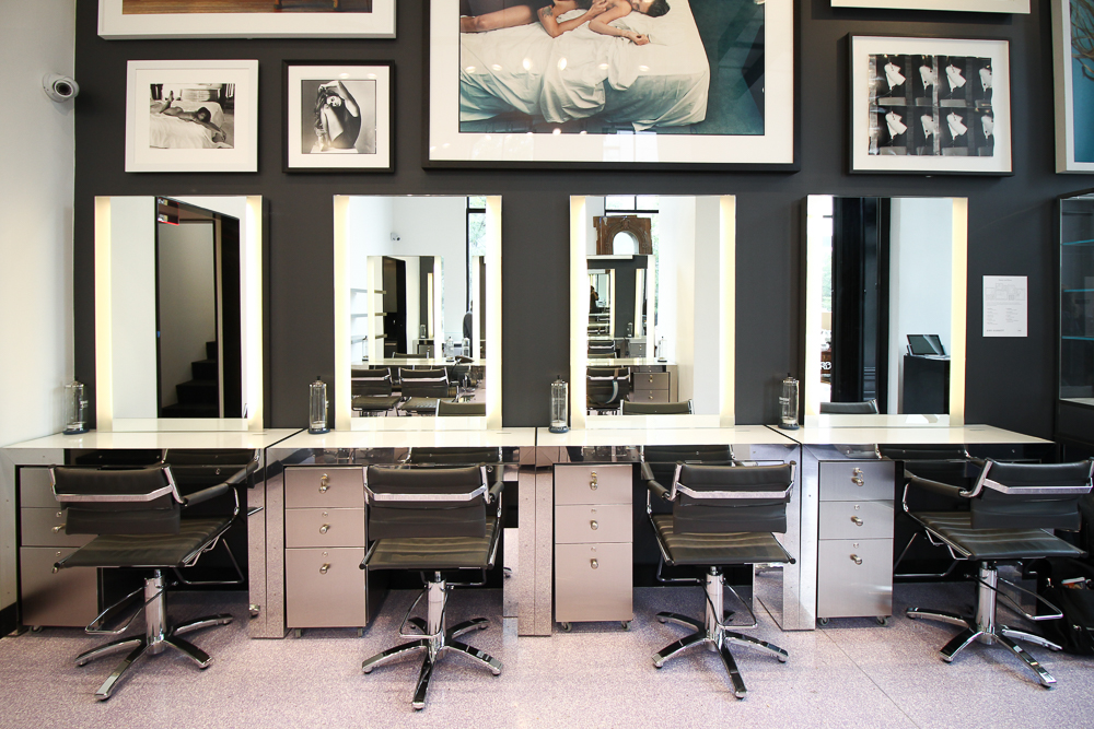 Beauty stations with bright mirrors and photographs displayed higher on the dark grey wall. MEP designed by 2L Engineering.
