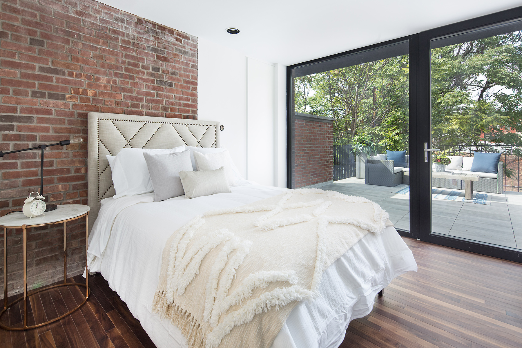 Bedroom with white sheets and a brick wall leading to a private balcony in a Brooklyn home. MEP designed by 2L Engineering.