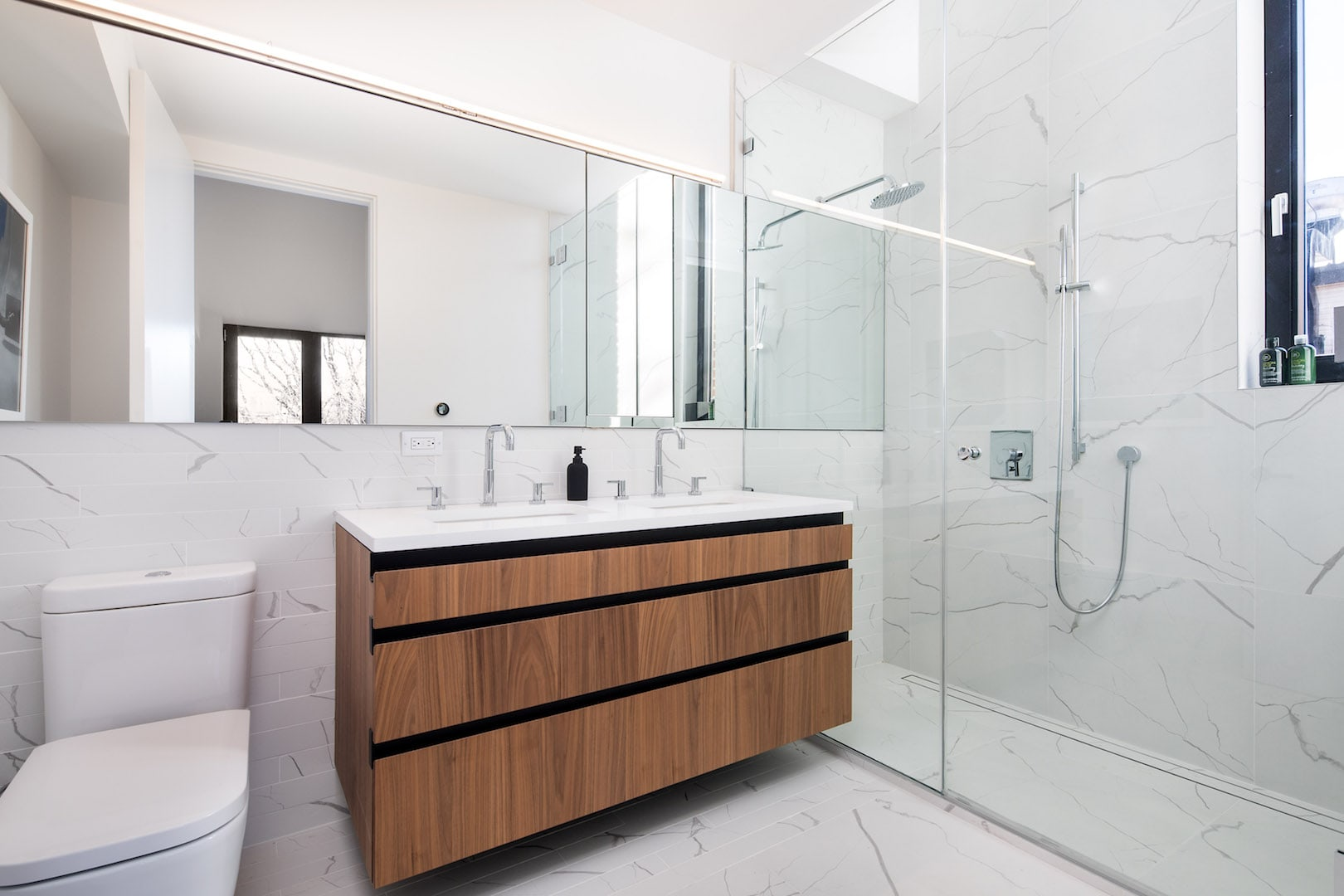 Minimalist bathroom with wood accent and marble tiling in a Brooklyn home. MEP designed by 2L Engineering.