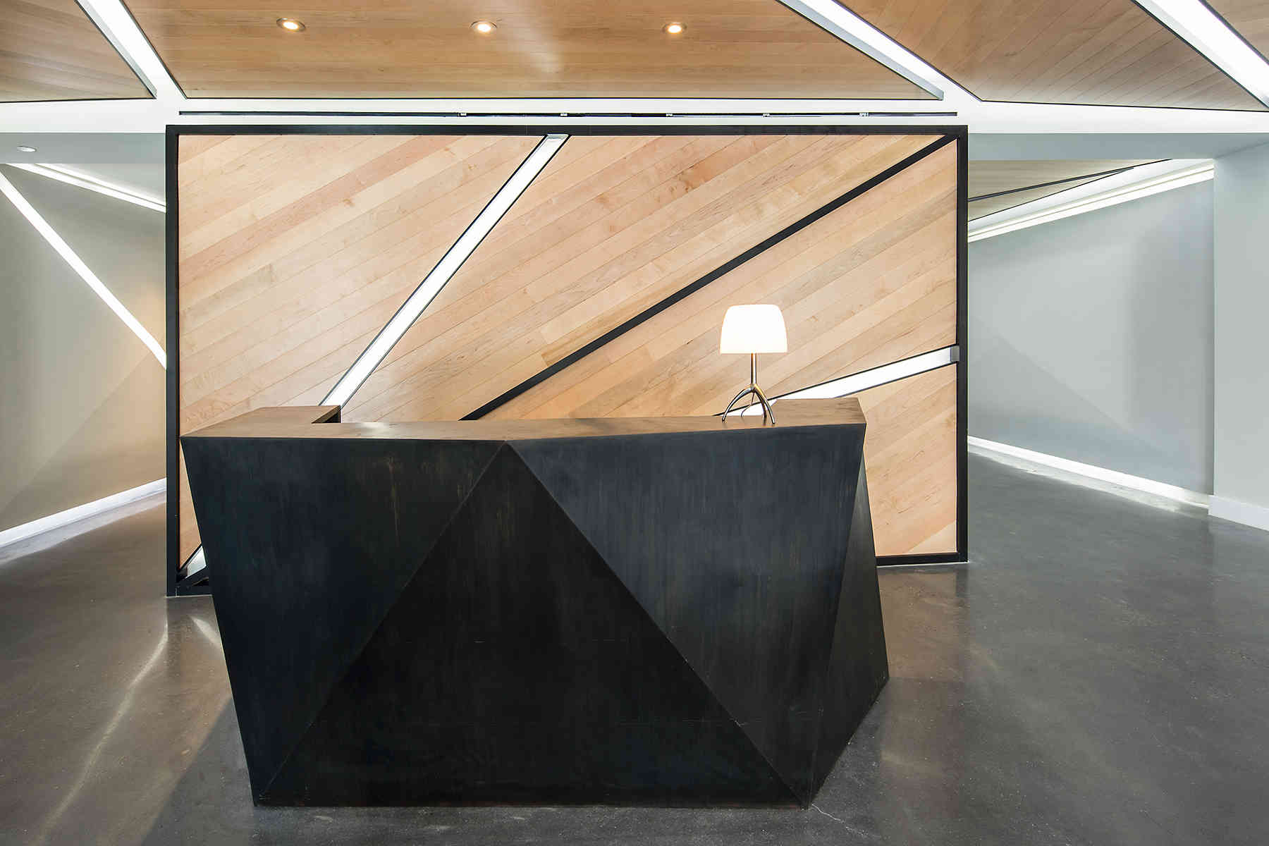 Reception area with a geometric, black desk and a modern lamp in front of a wood panel wall. MEP designed by 2L Engineering.