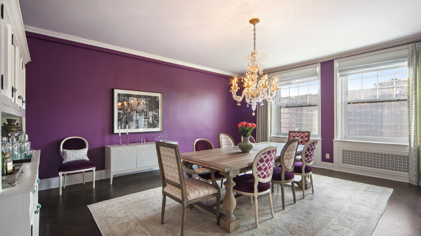 Bohemian dining room with a purple accent wall and mismatched chairs. MEP designed by 2L Engineering.