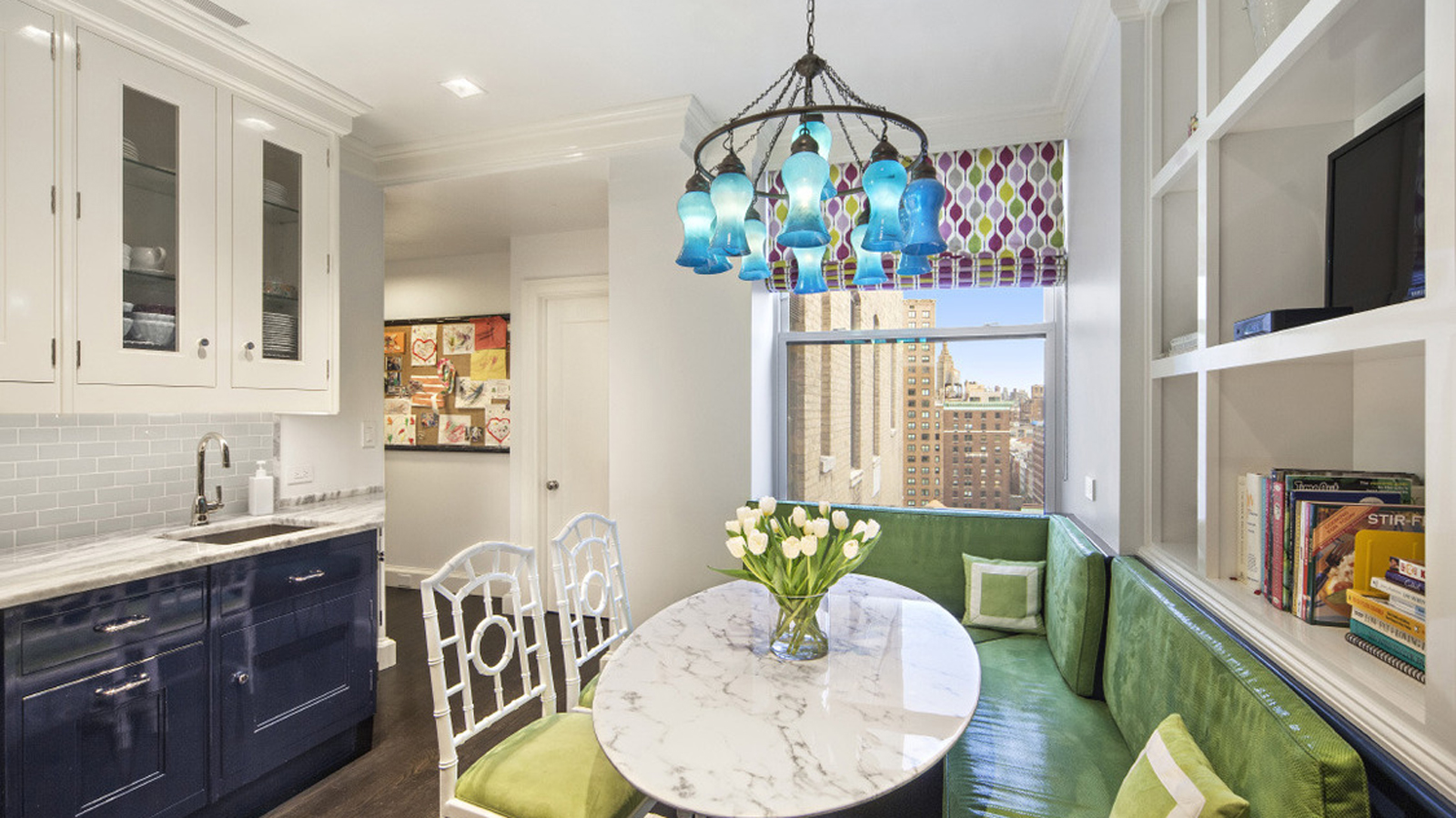 Breakfast nook with lime green seating and a light blue chandelier facing dark blue kitchen cabinets. MEP designed by 2L Engineering.