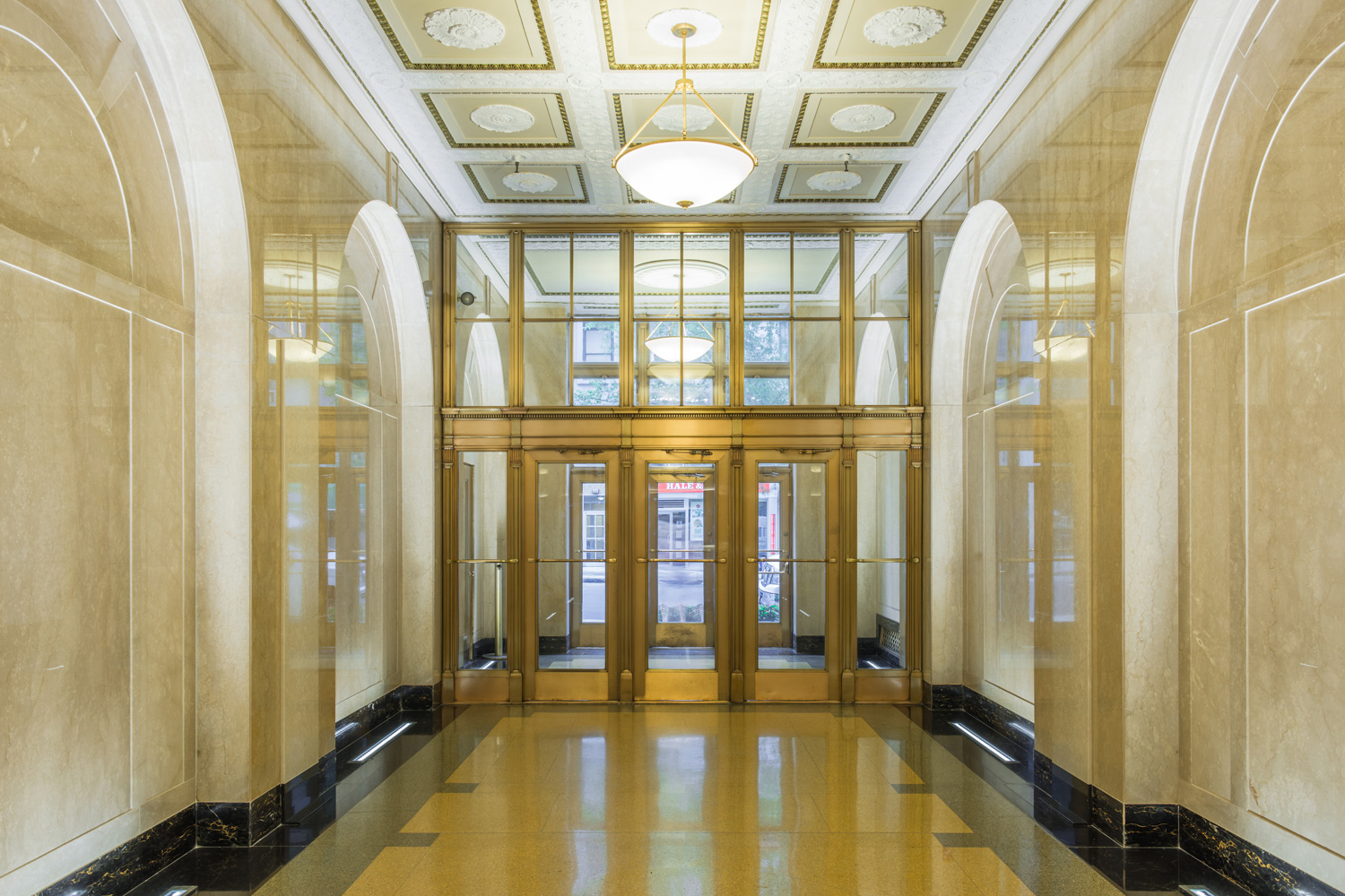Brightly lit and gold tinted lobby of 180 Madison. MEP Engineering provided by 2L Engineering.