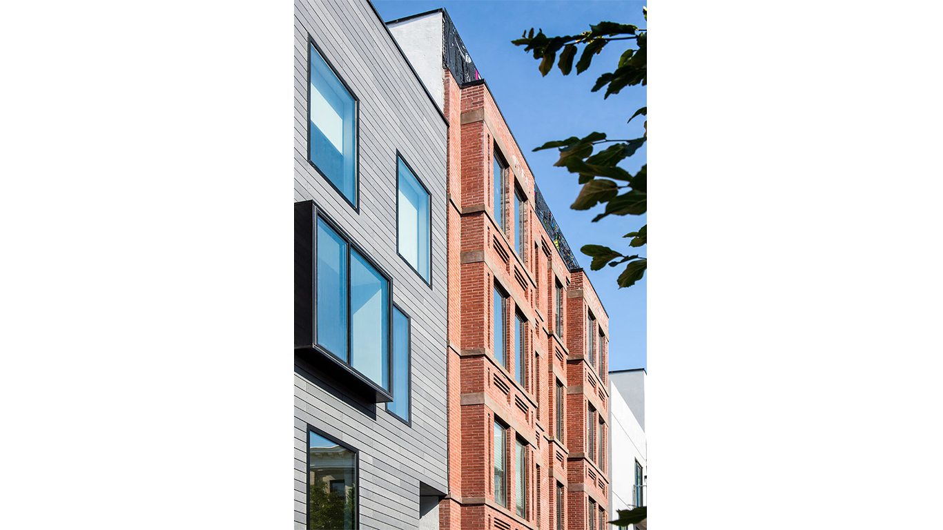 Brick and wood facade of a residential building in Brooklyn facing the sidewalk. MEP provided by 2L Engineering.