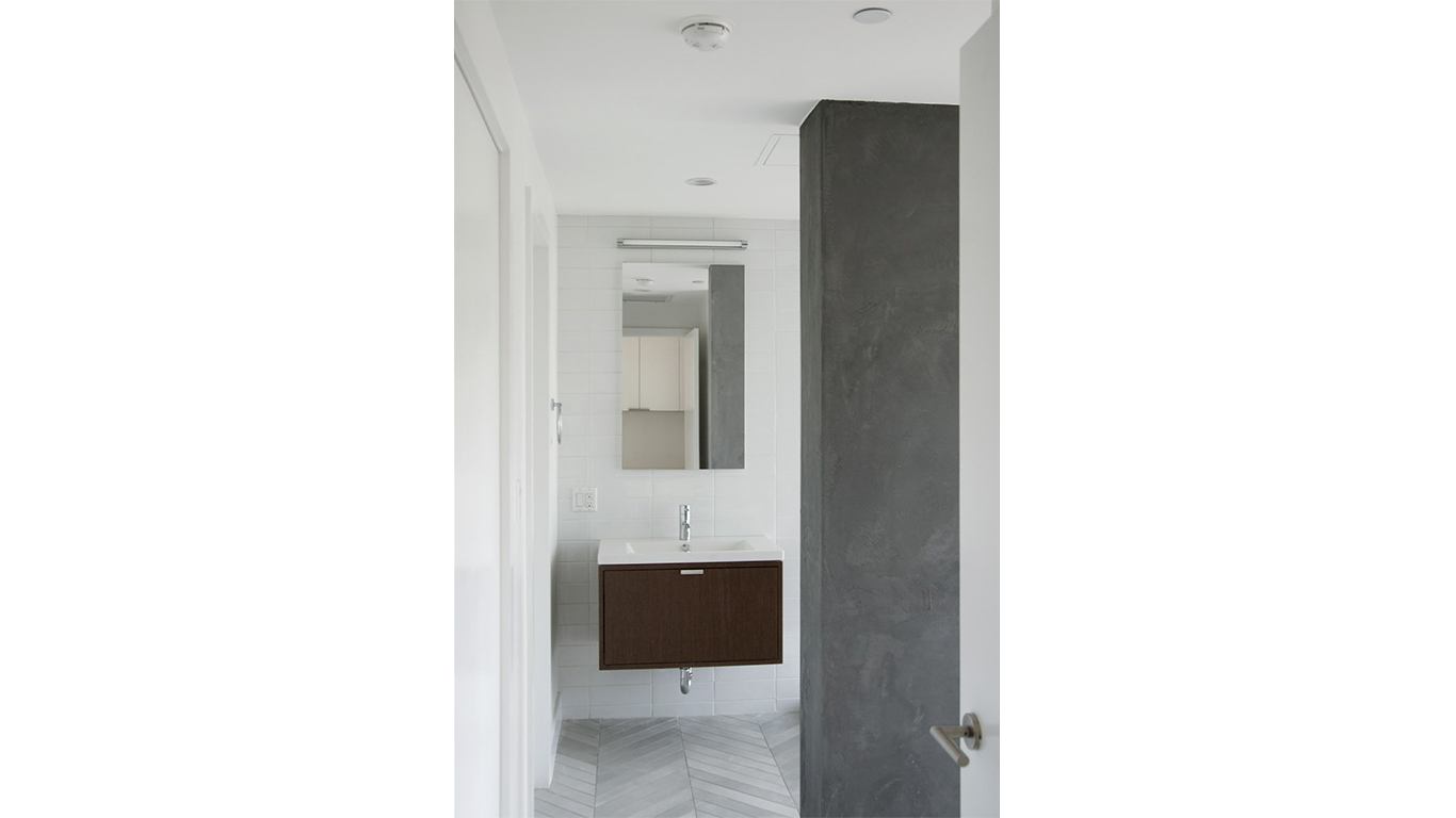 Modern, minimalistic bathroom with chevron tiles in a luxury residential home in Brooklyn. MEP designed by 2L Engineering.