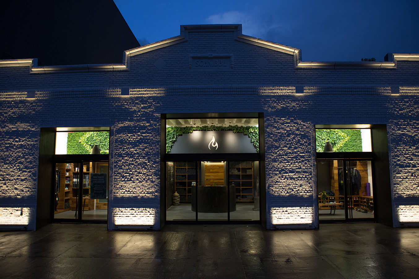 Light brick exterior of Modo Yoga with the brand's logo illuminated inside on a rainy evening in Brooklyn, New York. MEP designed by 2L Engineering.