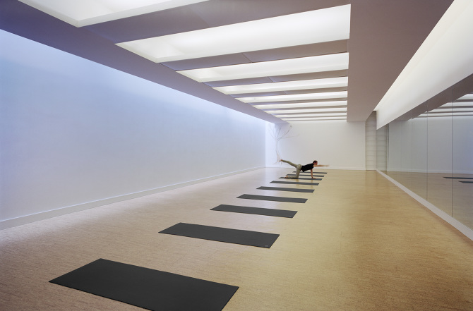 Person doing a yoga pose on a black mat facing a mirror in a studio at Modo Yoga, with MEP designed by 2L Engineering, a New York firm.
