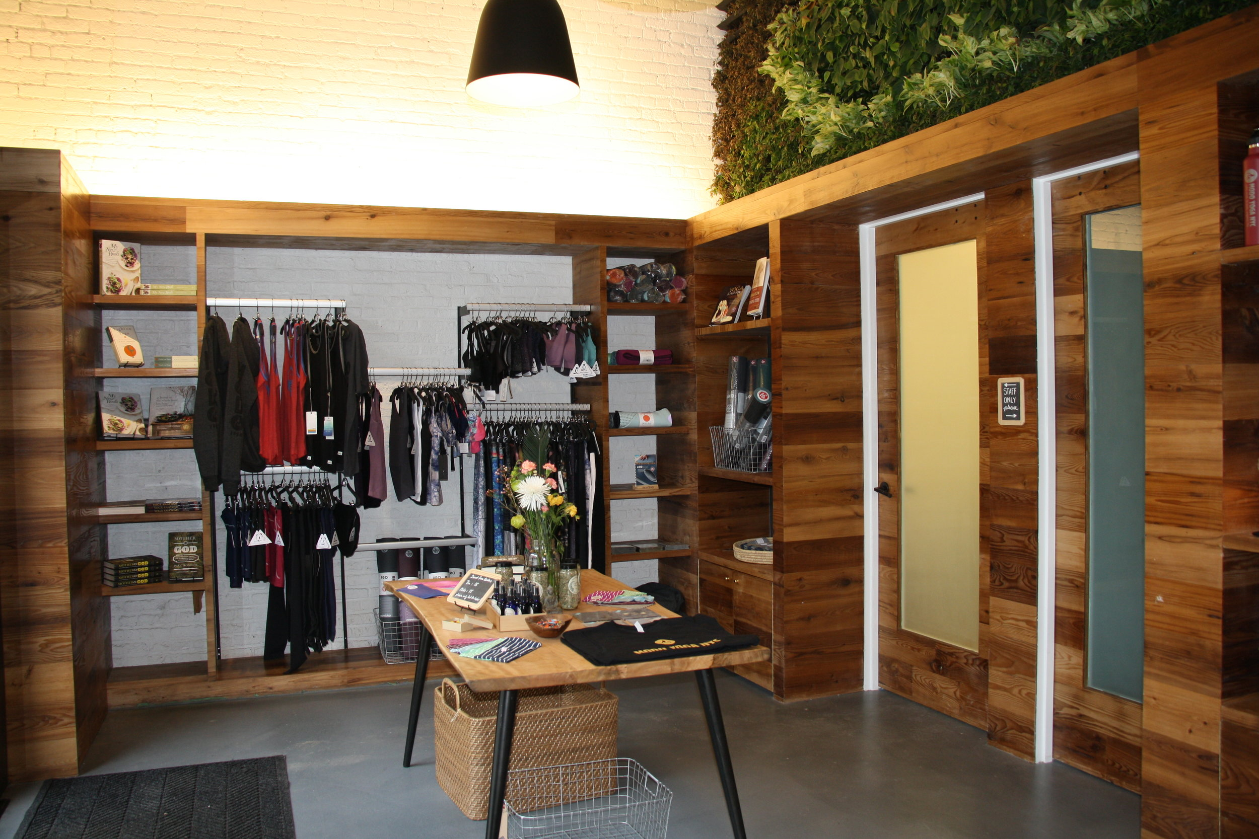 Retail space with athletic products on racks and display shelves for guests at Modo Yoga in Brooklyn, New York. MEP designed by 2L Engineering.