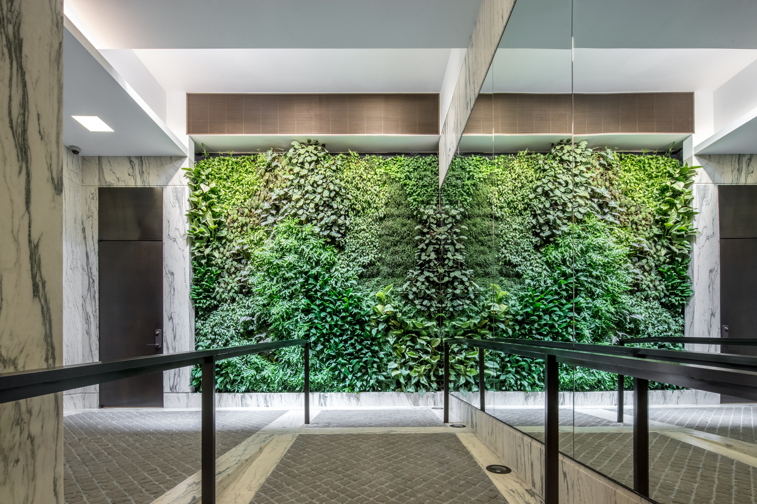 Front view of a brightly lit living green wall with tiled and marble flooring and a mirror facing the elevators. MEP provided by 2L Engineering.