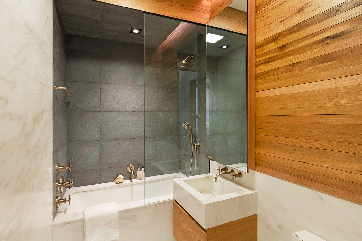 Wood paneled walls in a luxury bathroom featuring a bathtub and shower combo. MEP provided by 2L Engineering.