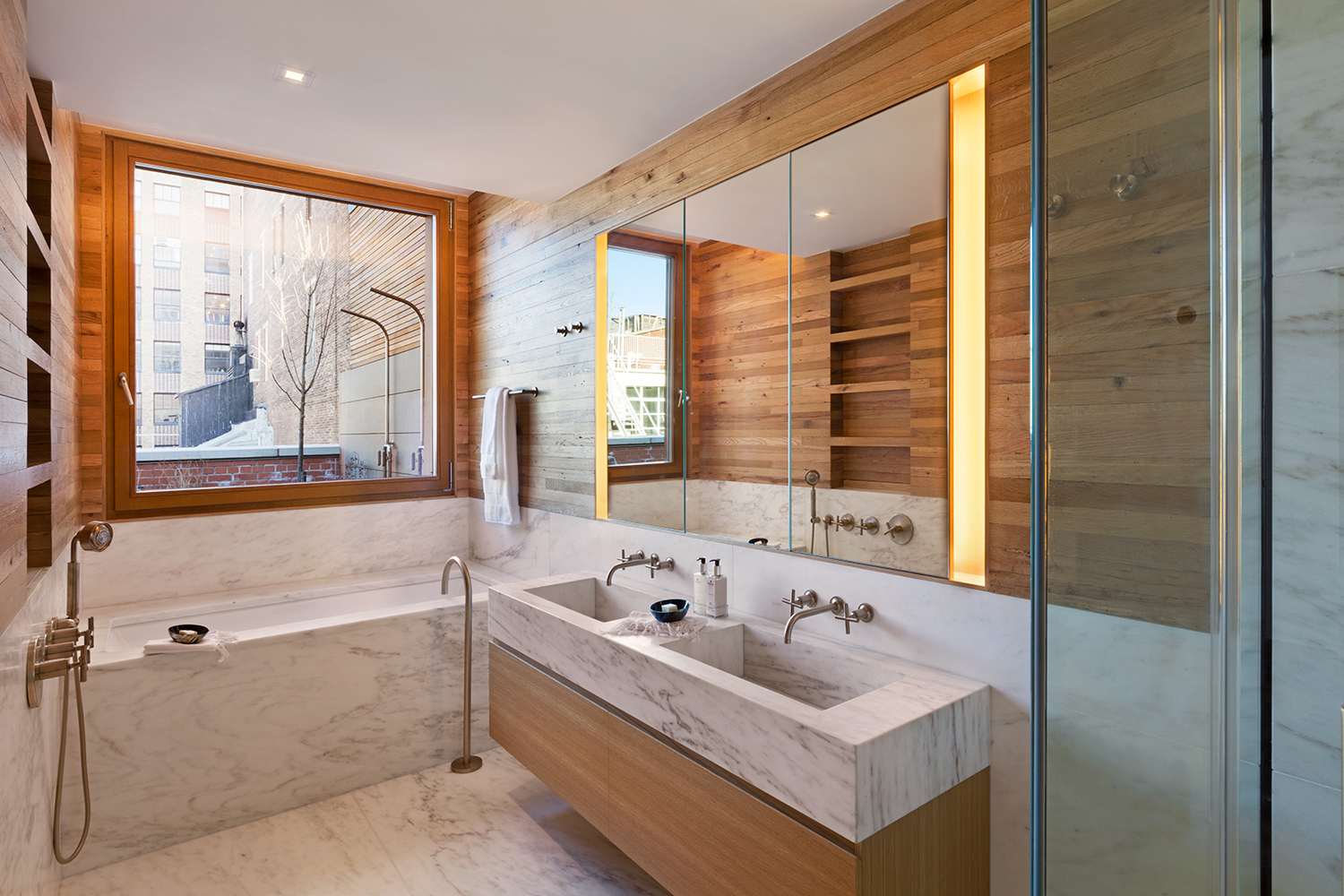 Wood paneled walls with marble accents in a luxury bathroom. MEP designed by 2L Engineering.
