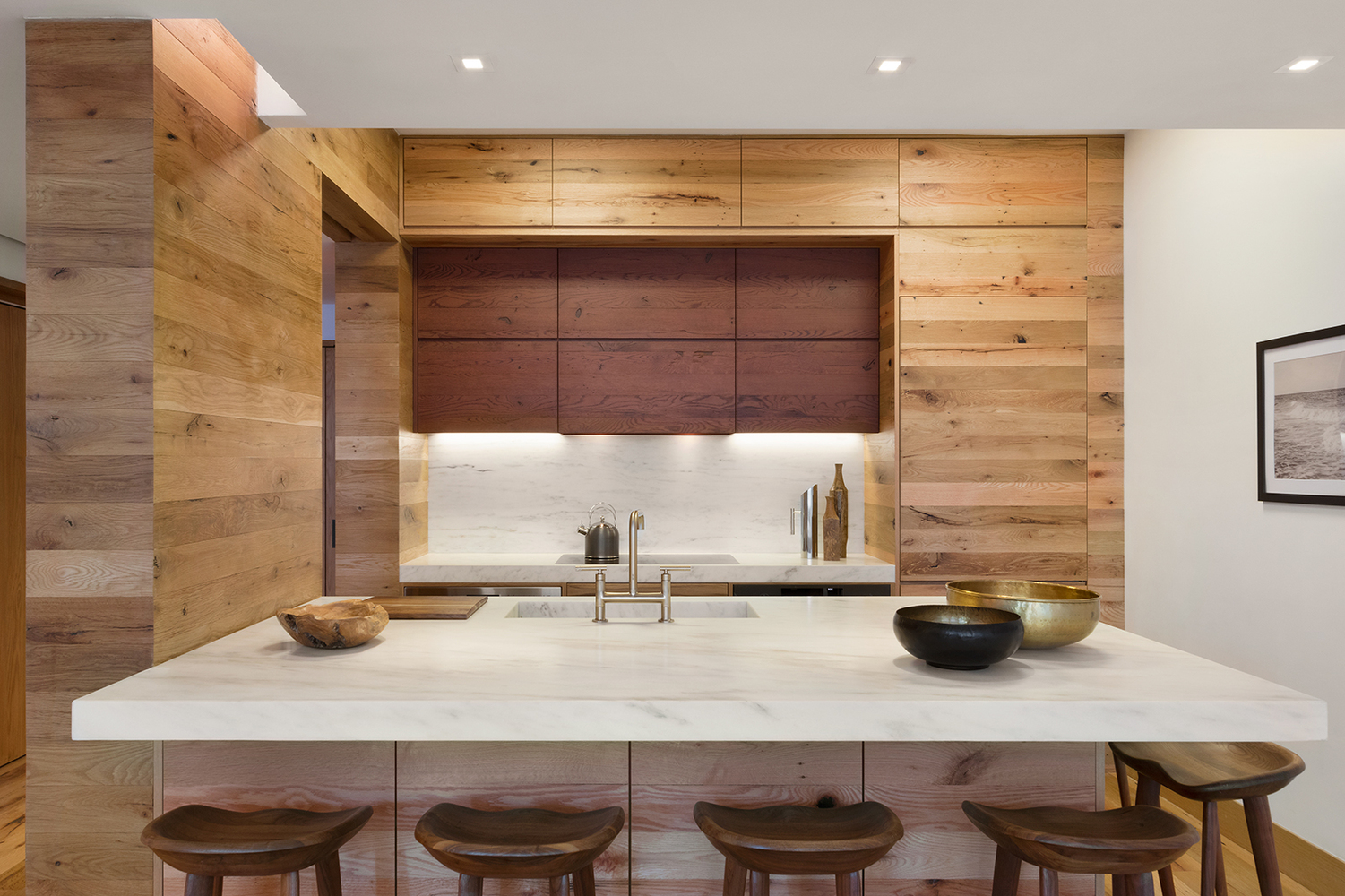 Wood paneled storage spaces in a rustic kitchen with marble counters and a teapot on the stove. MEP designed by 2L Engineering.