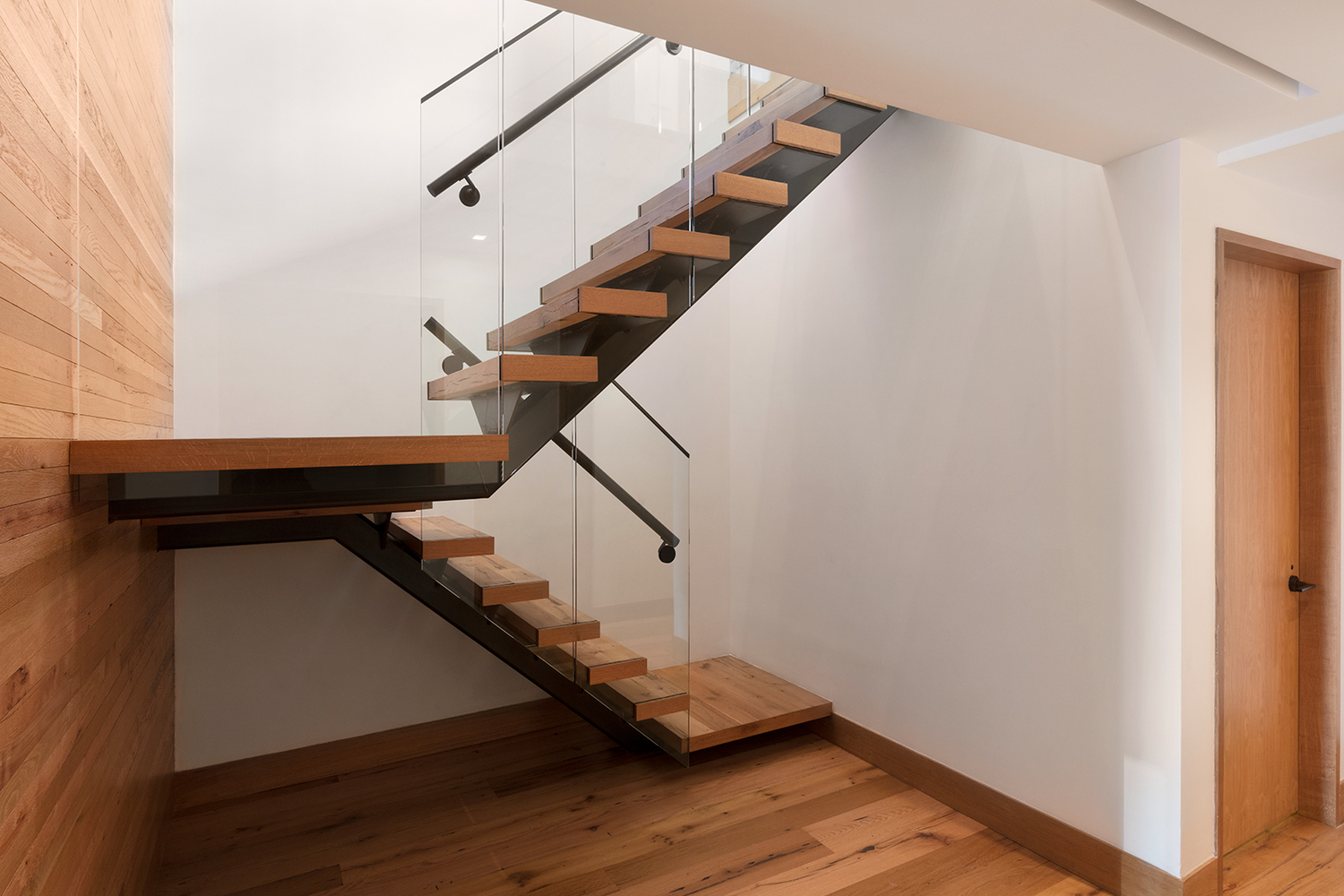 Wooden staircase with glass railing inside a luxury apartment featuring MEP work done by New York firm, 2L Engineering.
