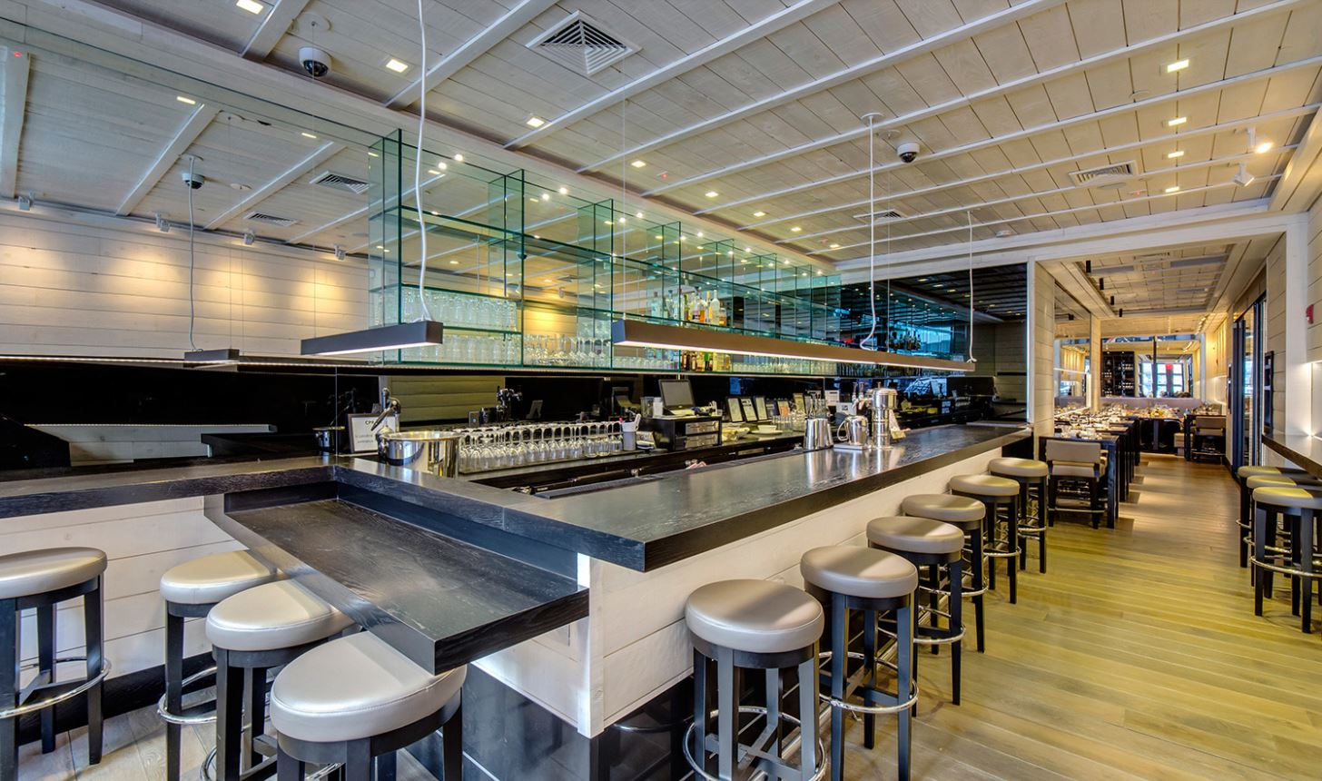 Grey bar seating facing glass shelving in Le Coq Rico, a sophisticated bistro and bar by a renowned French chef. MEP provided by 2L Engineering, a New York firm.