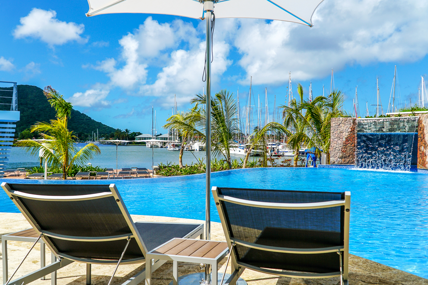 Lounge chairs by the pool facing a harbor where boats are anchored at the Harbor Club Hotel. MEP designed by 2L Engineering..