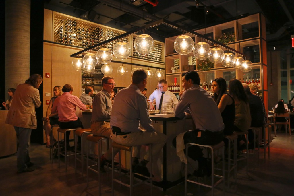 People enjoying dinner sitting by the bar were a bartender prepares drinks at Tarallucci e Vino in New York. MEP provided by 2L Engineering.