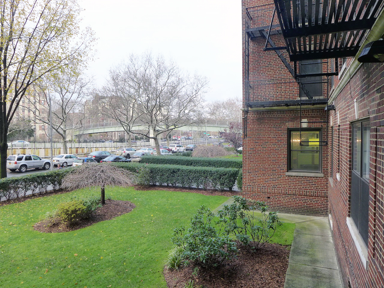 View of the front lawn of 31 Ocean Parkway, with cars parked on the street facing a walking bridge. MEP designed by 2L Engineering.