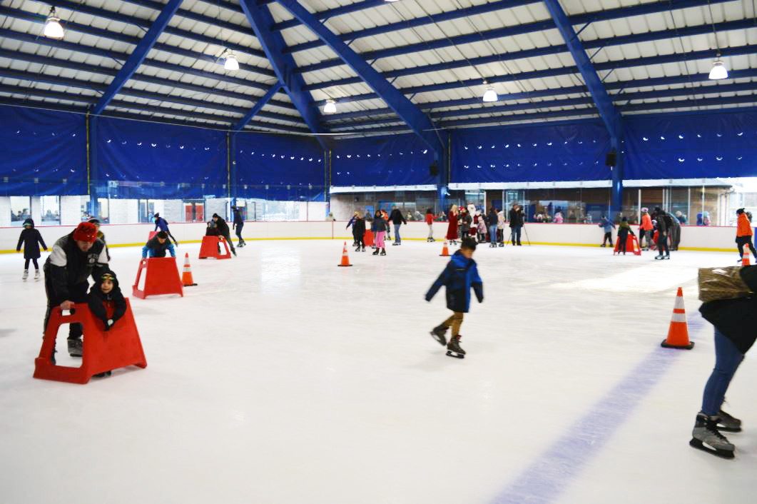 Different people skating with orange guides in the brightly lit Secaucus Ice Skating Rink in New Jersey with MEP designed by 2L Engineering.