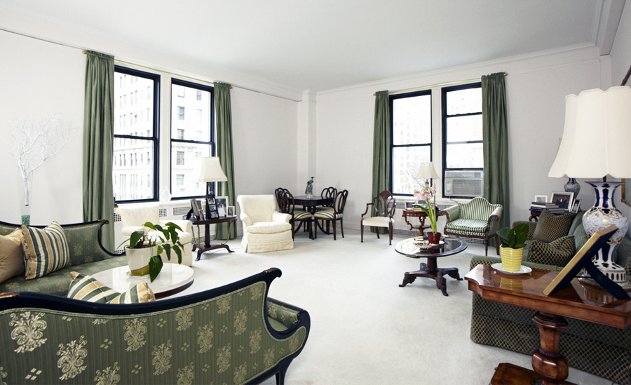 The lounge area of a Park Avenue apartment with green details such as forest green curtains, and printed green seating. MEP provided by 2L Engineering.