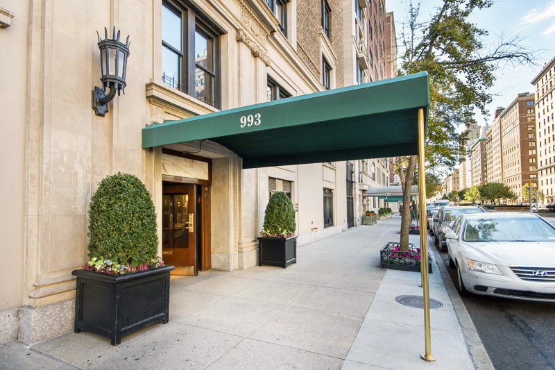 Entrance to a residential building on Park Avenue, New York, with bushes on the sides and a green awning. MEP designed by 2L Engineering.
