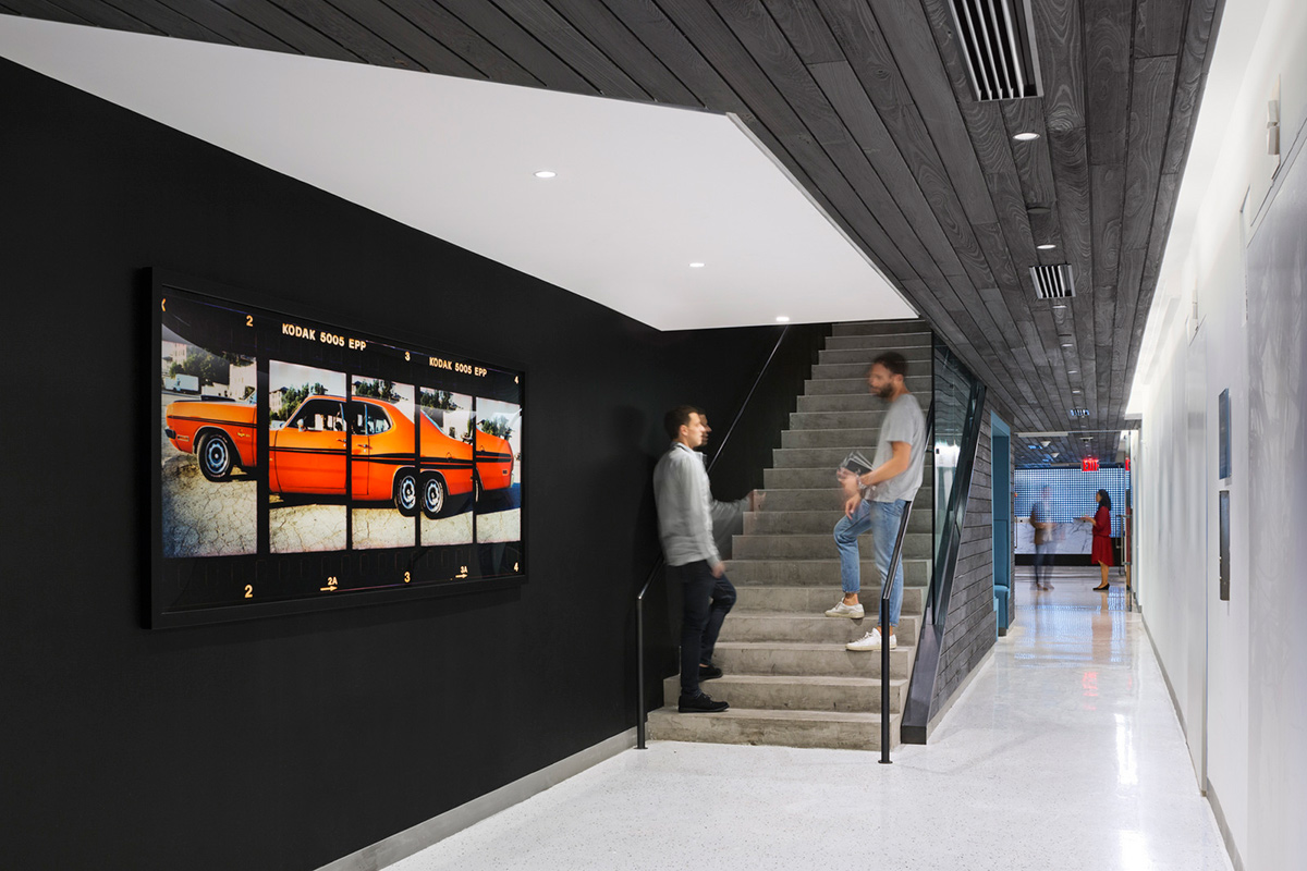 Two men having a conversation on the stairs beside artwork of an orange car in the offices of Droga5. MEP Provided by 2L Engineering.