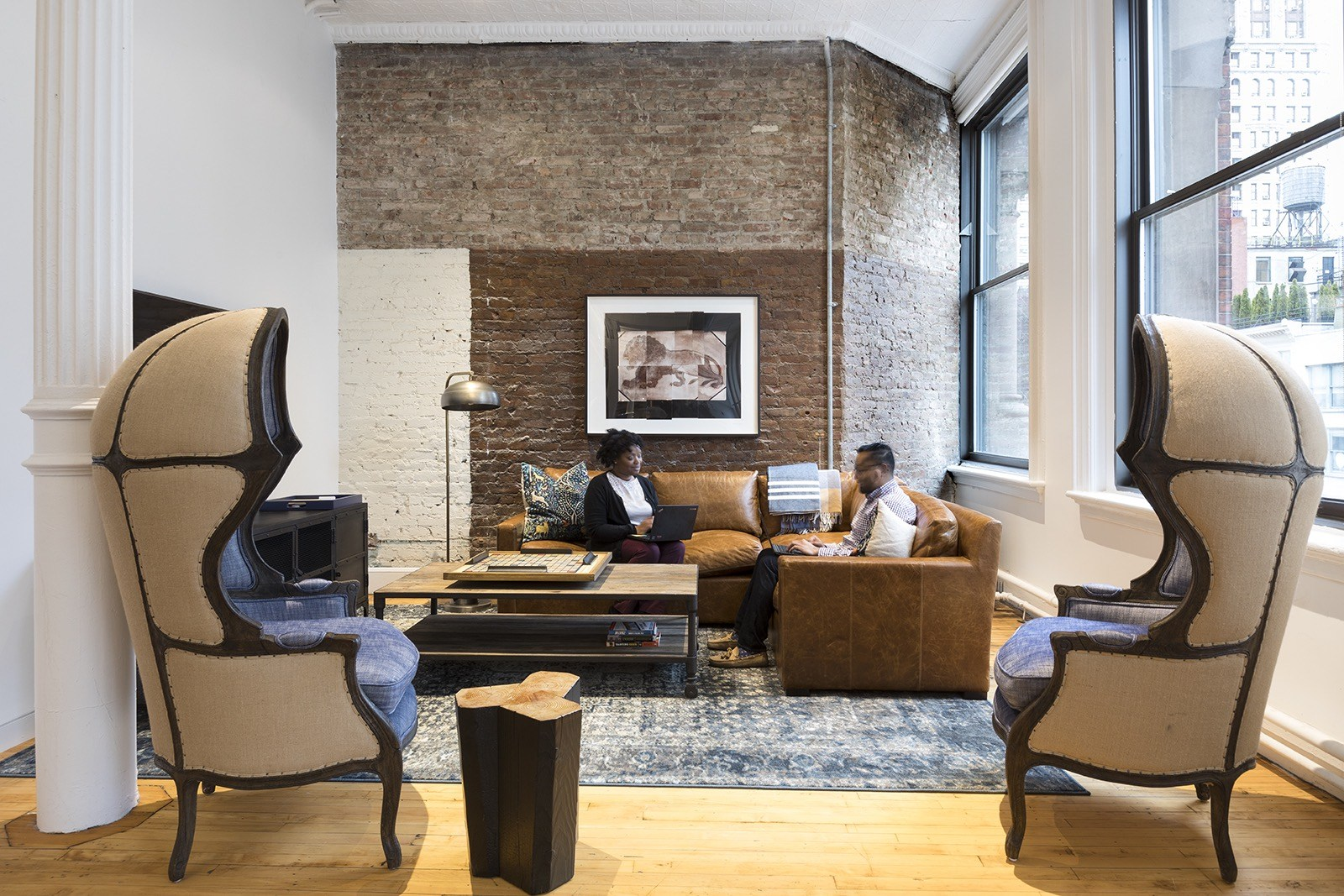 People sitting and working together in a rustic designed lounge area in the New York office of Edrington Spirits, a privately owned international spirits company. MEP by 2L Engineering..