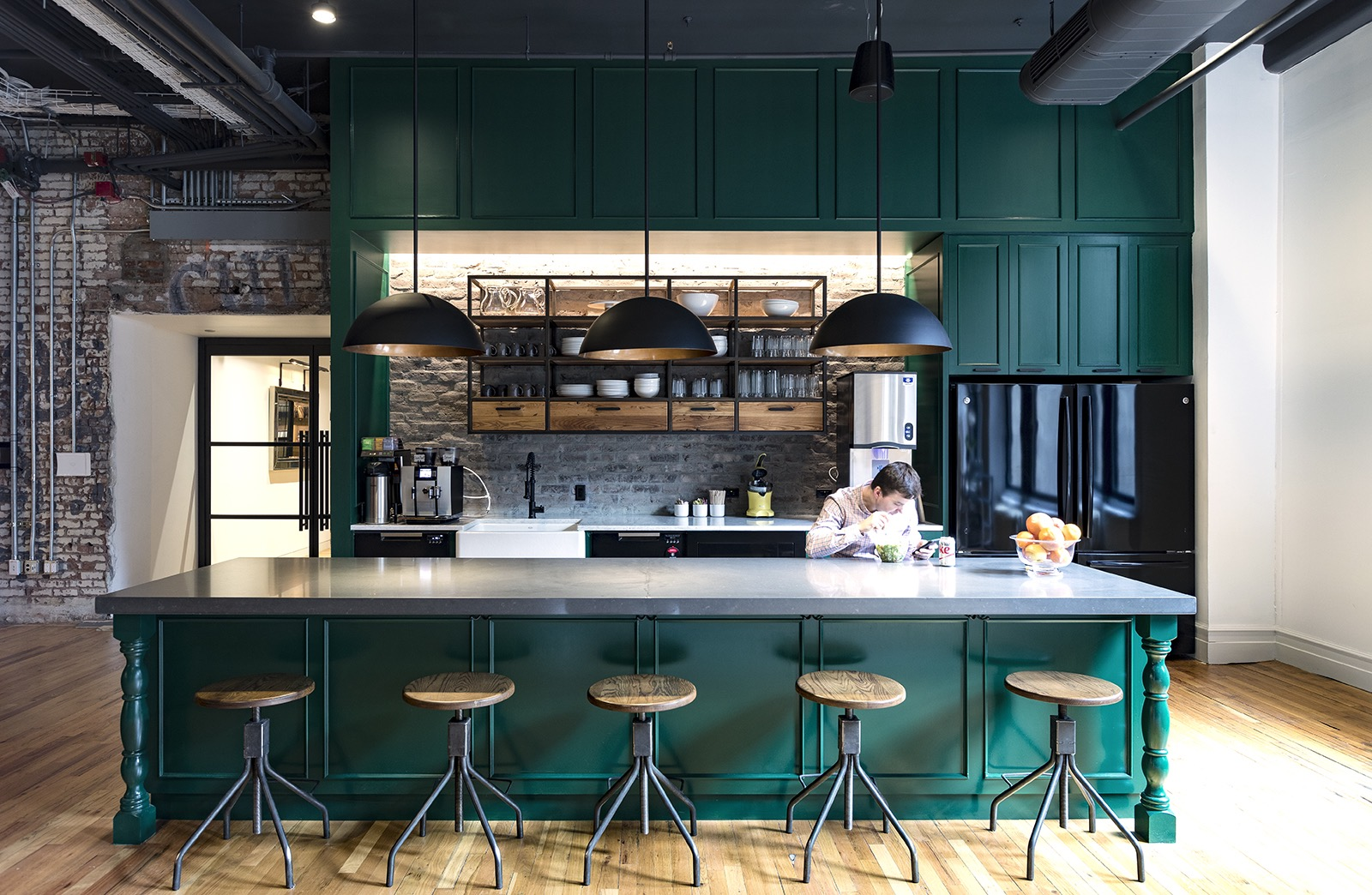 Man eats a salad and has diet coke, checking his phone and sitting by the bar of a green-accented rustic kitchenetter in Edrington Spirits office. 2L Engineering.