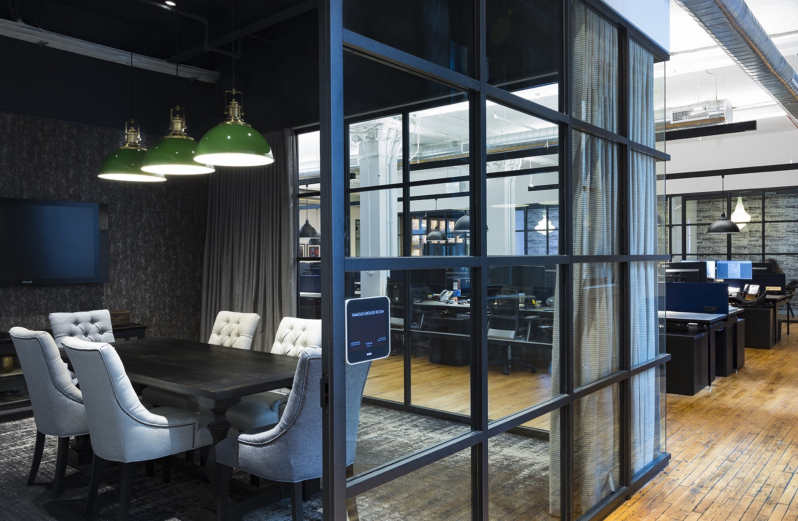 Darkly decorated private conference room with glass partitions in the office of Edrington Spirits. MEP designed by 2L Engineering.