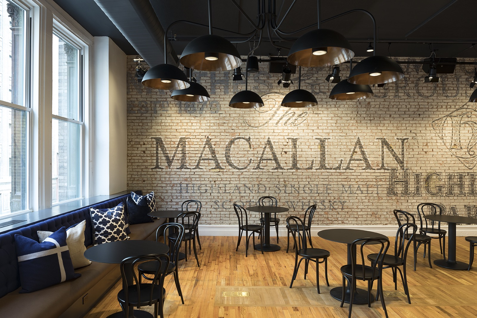 Black chairs and tables beside a brick wall with names of whiskey brands managed by Edrington Spirits. MEP designed by 2L Engineering.