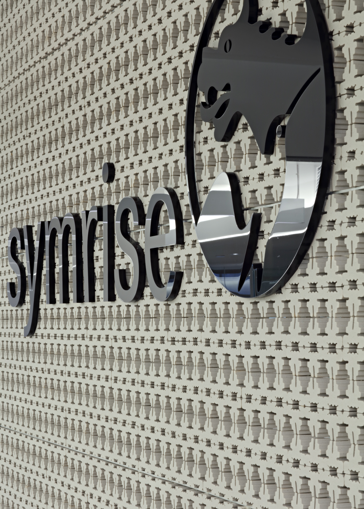 Symrise reception desk with fragrance products on a display shelf and the company logo. MEP designed by 2L Engineering.