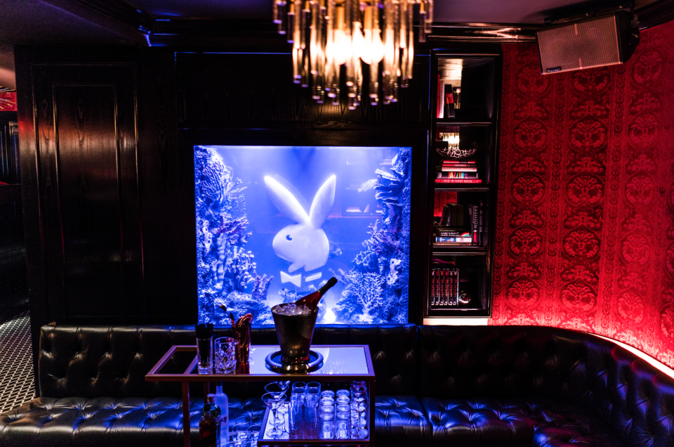 Custom aquarium behind black leather lounge seats featuring the famous Playboy bunny logo in the Playboy Club, New York. MEP services provided by 2L Engineering.