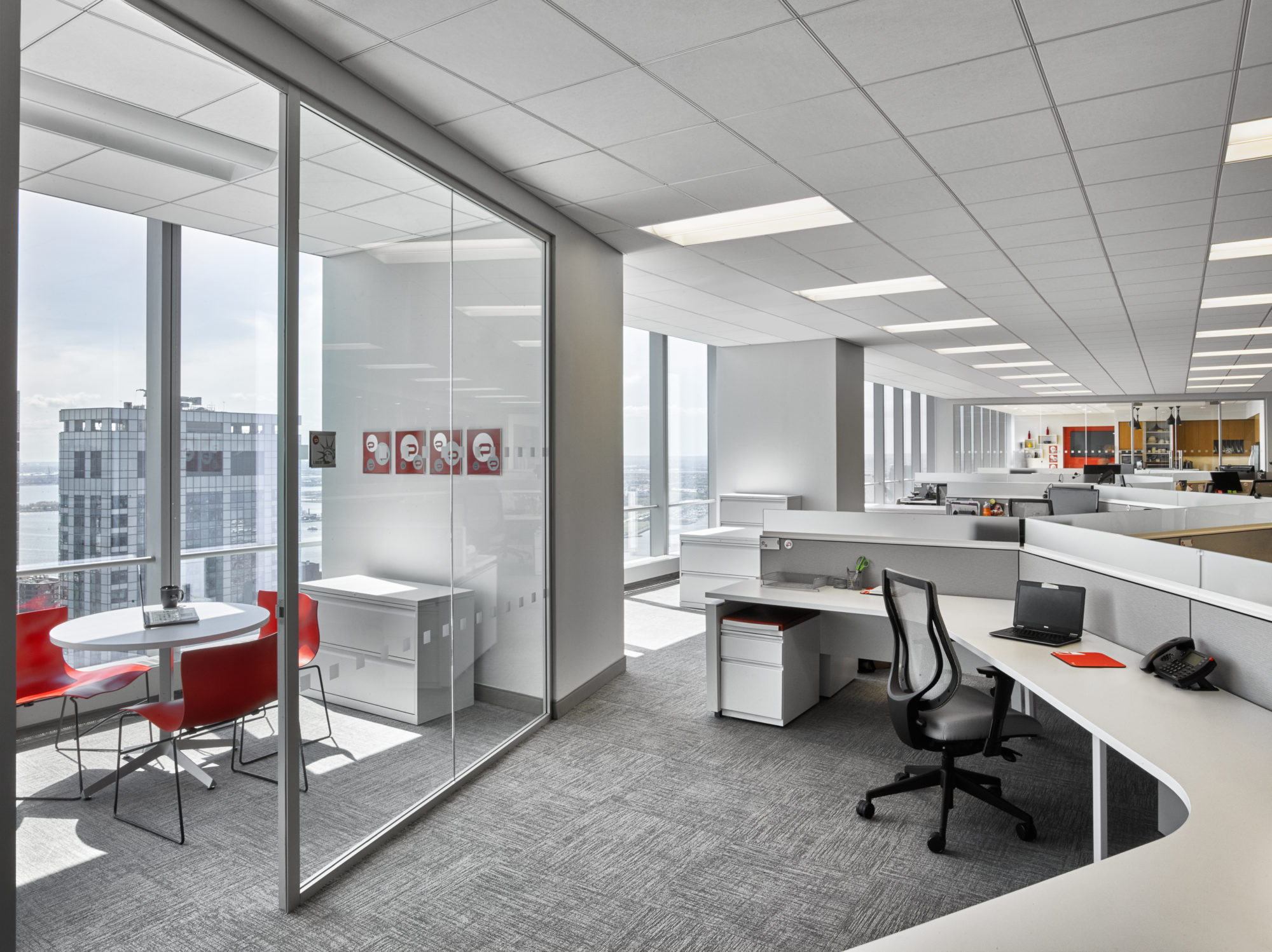 Small private meeting room beside open working spaces in the offices of Padilla CRT, a communications agency located in New York. MEP by 2L Engineering.