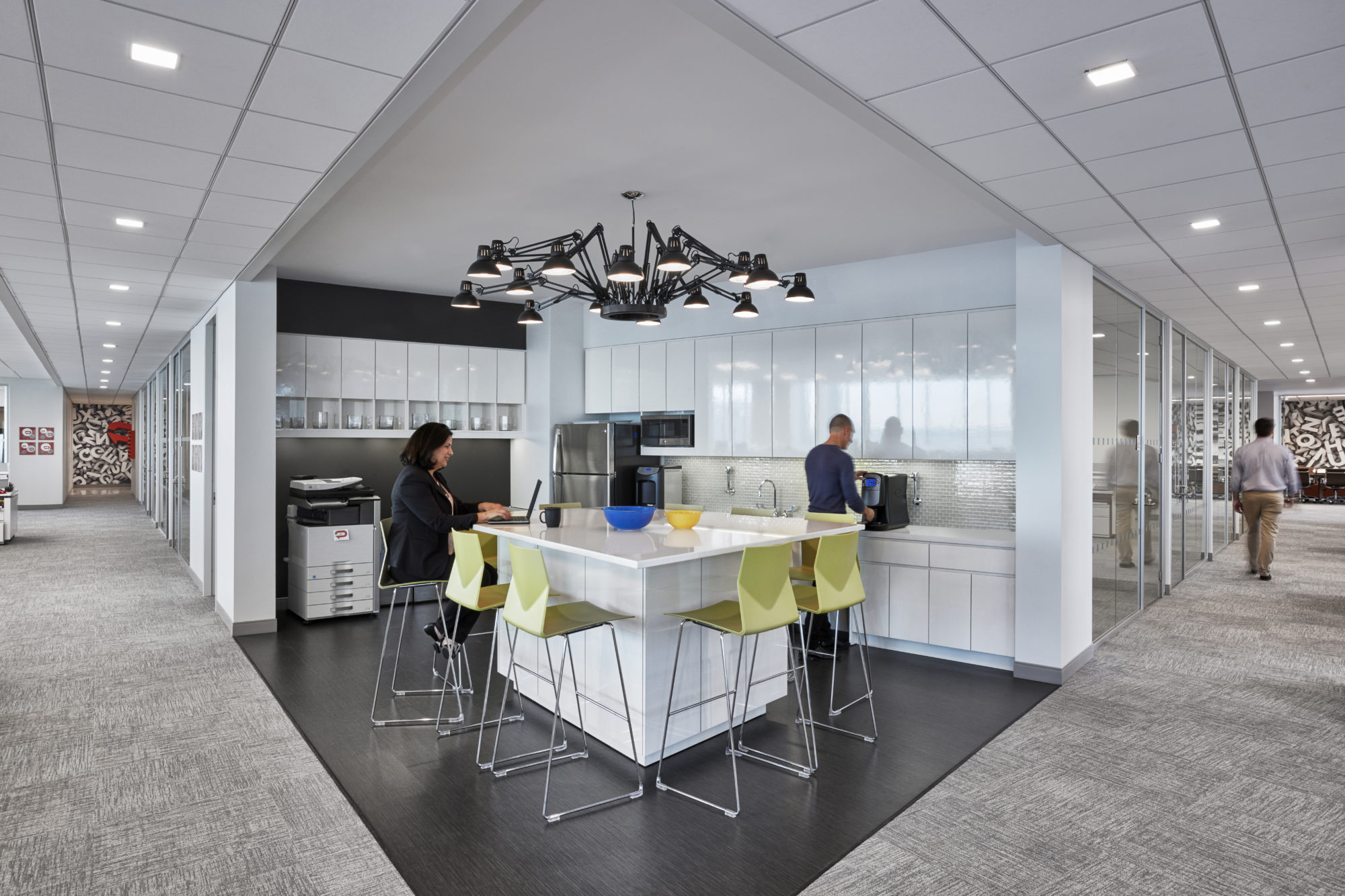 Office kitchenette with a desk lamp chandelier and green bar seats where a woman is working on her laptop as a man makes coffee. MEP provided by 2L Engineering.